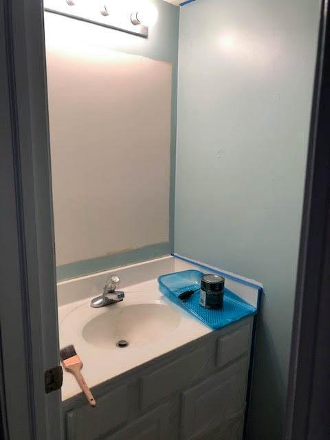Boring builder half bath with builder grade bathroom lighting